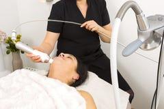 La femme atteignent le traitement de visage la clinique de beauté Image libre de droits