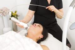 La femme atteignent le traitement de visage la station thermale de beauté Images libres de droits