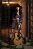 La femme attirante avec le regard de pays, a à l'intérieur tiré, style campagnard américain Fille avec le chapeau et la guitare d Image libre de droits