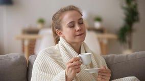 La femme attirante couverte du café potable de matin de plaid se sent heureuse banque de vidéos