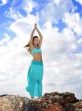 La femme attirante dans la pose de yoga de zen au dessus de montagne de roche détendent dedans Photos libres de droits