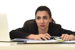 La femme attirante dans le fonctionnement de costume a fatigué et était ennuyeuse dans le bureau d'ordinateur de bureau semblant  images stock