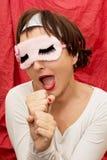 La femme attirante dans le masque de sommeil imite le chant dans un microp Image stock