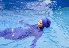 La femme attirante dans un burkini musulman de vêtements de bain nage dans la piscine photo stock