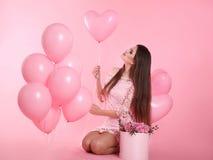 La femme attirante de brune d'amour avec les ballons et le bouquet de s'est levée Image stock
