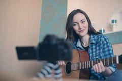 La femme attirante de brune dans la chemise de plaid bleue avec la guitare s'enregistre à disposition sur la vidéo image libre de droits