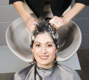 La femme attirante obtient le shampooing et la révision de salon de station thermale images stock