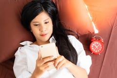 La femme attirante se réveille dans le matin sur un lit La belle fille de charme joue l'Internet en ligne sur le téléphone portab photo stock