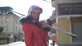 La femme attirante tient les maisons proches la tenant ski incliné avant le ski photos stock