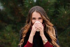 La femme attirante a une pause-café sur la rue dans le jour d'automne photographie stock