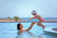 La femme attrape la fille sautant dans le regroupement contre la mer Photos libres de droits