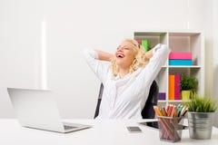 La femme au bureau s'est penchée de retour dans sa chaise Images stock