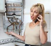 La femme au foyer appelle dans un atelier sur la réparation des chauffe-eau de gaz Image libre de droits