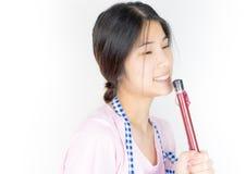 La femme au foyer asiatique heureuse chante photographie stock
