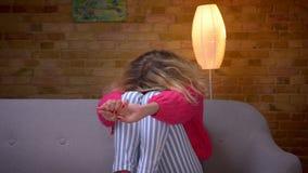 La femme au foyer blonde dans le chandail rose sur le sofa regardant la TV obtient terrifiée et cache son visage à la maison conf clips vidéos