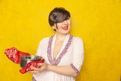 La femme au foyer caucasienne prépare un repas la brune se tient dans un peignoir avec une casserole et des supports de pot sur u photos libres de droits