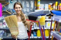 La femme au foyer choisit le balai pour le nettoyage Photo libre de droits
