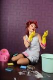La femme au foyer dans des bigoudis de cheveux et des gants en caoutchouc peint le rouge à lèvres de lèvres photographie stock libre de droits