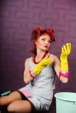 La femme au foyer dans des bigoudis de cheveux et des gants en caoutchouc peint le rouge à lèvres de lèvres images libres de droits