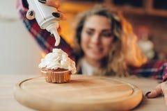 La femme au foyer dans le tablier couvre le dessert doux de la crème photo libre de droits