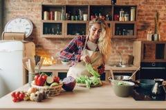 La femme au foyer dans le tablier prépare la salade sur la cuisine images stock