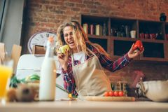 La femme au foyer dans un tablier joue avec le poivre frais photographie stock libre de droits