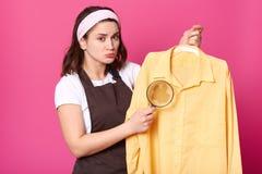 La femme au foyer de brune tient la chemise jaune après blanchisserie avec la tache de café sur le tissu, ayant la loupe dans une photo stock