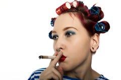 La femme au foyer de Funy avec des bigoudis fume une cigarette coupure de tabagisme pour la dame sexy L'espace libre pour votre t image libre de droits