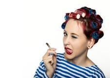 La femme au foyer de Funy avec des bigoudis fume une cigarette coupure de tabagisme pour la dame sexy L'espace libre pour votre t photographie stock