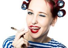 La femme au foyer de Funy avec des bigoudis fume une cigarette coupure de tabagisme pour la dame sexy L'espace libre pour votre t photo stock