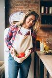 La femme au foyer de sourire maintient les légumes frais dans le tablier photographie stock libre de droits