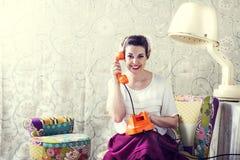 La femme au foyer de vintage cause au téléphone dans le salon de coiffure Photo stock