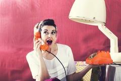 La femme au foyer de vintage cause au téléphone dans le salon de coiffure photographie stock libre de droits