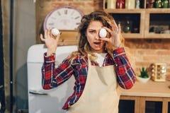 La femme au foyer espi?gle a couvert ses yeux d'oeufs image stock