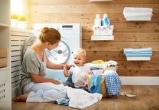 La femme au foyer et les enfants heureux de mère de famille dans la blanchisserie chargent W images libres de droits