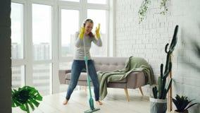 La femme au foyer heureuse est dansante et chantant pendant faire le ménage, elle écoute la musique dans les écouteurs et le plan banque de vidéos