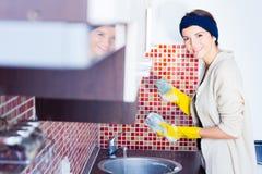 La femme au foyer lave un verre Images stock