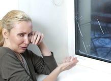 La femme au foyer pleure, mauvaise fenêtre de qualité a éclaté en raison du temps froid Photo stock