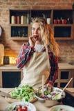 La femme au foyer s'assied sur la table et juge la tomate disponible photographie stock libre de droits