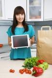 La femme au foyer utilise une tablette dans la cuisine Photographie stock libre de droits