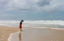 La femme aux pieds nus dans le chapeau et la robe regarde vers le bas sa boue couverte des pieds sur la plage sur la Gold Coast d Photos libres de droits