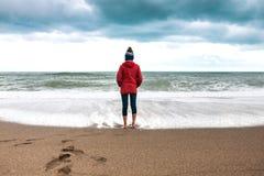 La femme aux pieds nus regarde la mer d'hiver images stock