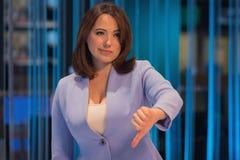 La femme avec émotion pessimiste dans un studio de télévision montre un geste des doigts au fond images libres de droits