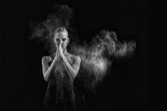 La femme avec arrêtent le mouvement de la poudre explosive capturé par l'éclair Images stock