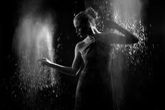 La femme avec arrêtent le mouvement de la poudre explosive capturé par l'éclair Photographie stock