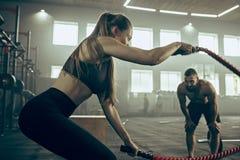 La femme avec la bataille ropes l'exercice dans le gymnase de forme physique image libre de droits