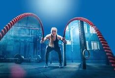 La femme avec la bataille ropes l'exercice dans le gymnase de forme physique images libres de droits