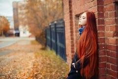 La femme avec de longs cheveux rouges marche en automne sur la rue Regard rêveur mystérieux et l'image de la fille Marche rousse  Photos stock
