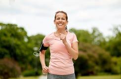 La femme avec des écouteurs ajoutent le brassard pulsant au parc photos stock