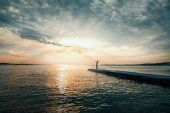 La femme avec des bras a soulevé la position sur le pilier au coucher du soleil Photographie stock libre de droits